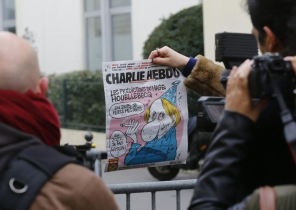 A cameraman shows the front page of Charlie Hebdo which shows a caricature of French author Michel Houellebecq, author of a new book about a fictional Muslim takeover of France, near the weekly's Paris offices after a shooting Jan 7, 2015. REUTERS/Jacky Naegelen.