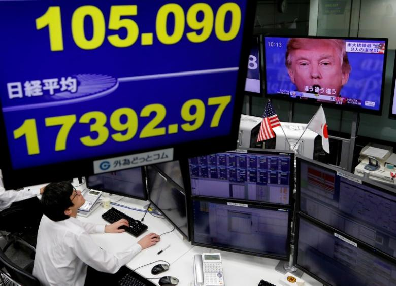 U.S. allies are uncertain about Trump's future trade policies. Here an employee in a Tokyo foreign-exchange company watches TV news about the new U.S. president-elect, November 9, 2016.   REUTERS/Toru Hanai