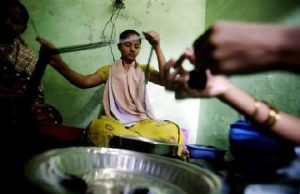 A customer of a micro finance institution strings beads into necklaces at a workshop in a slum area in Mumbai February 17, 2007. Reuters